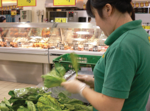Survival of the greenest: A staff in Giant hypermarket at Vivocity was spotted filtering crinkly vegetables at 3pm on a Monday (Source: Food Waste Republic)